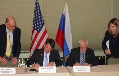 Two men seated at table signing documents.
